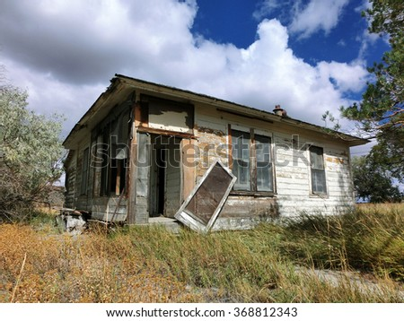 Abandoned prairie shack with broken windows and door - landscape photo - stock photo