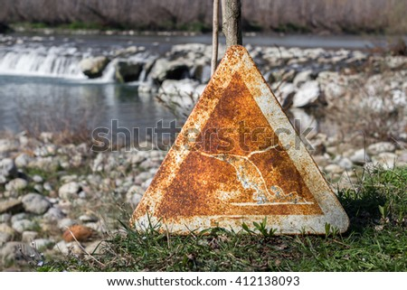 Abandoned road traffic sign with a flood warning. A river on the background. - stock photo