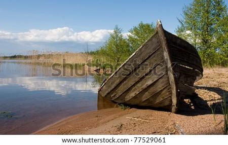 Abandoned rowboat left at the beach - stock photo