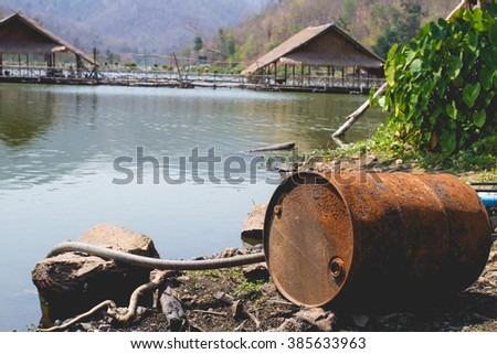 Abandoned rusty oil barrel near the lake with Raft houses on background - stock photo