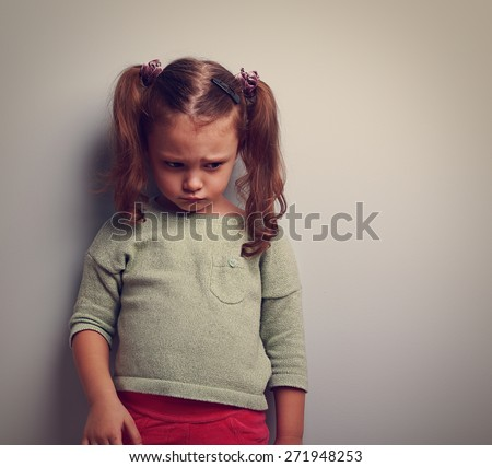 Abandoned sad kid looking down with pain on face. Closeup vintage portrait with empty copy space - stock photo
