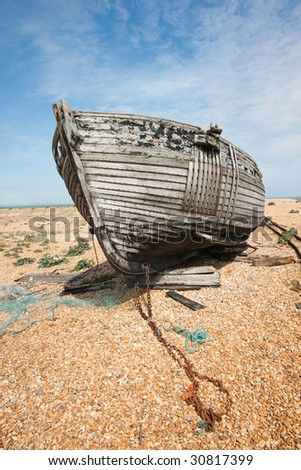Abandoned shipwreck of wood fishing boat on beach against blue sky - stock photo