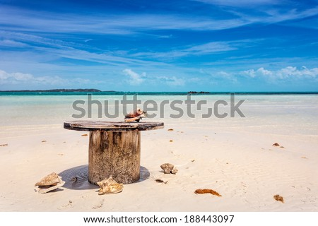 Abandoned table on the beach about to flood with the tide, Five Cays, Providenciales, Turks and Caicos - stock photo