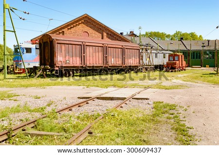 Abandoned trains and cars outside an old service depot with railroad tracks leading up to building. Small railway crossing in foreground. No person visible. - stock photo