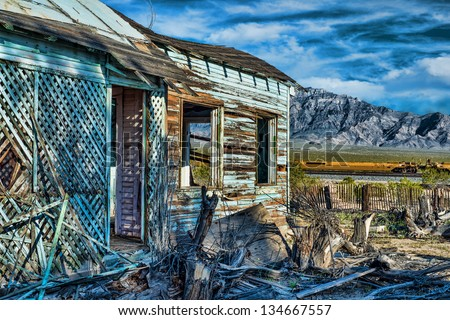 Abandoned turquoise house in Mojave National Preserve with old picket fence train tracks and dramatic mountains in the background - stock photo