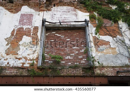 Abandoned warehouse exterior with brick wall, green vines, metal frame, and peeling paint - stock photo