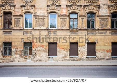 Abandoned weathered street wall with some windows - stock photo