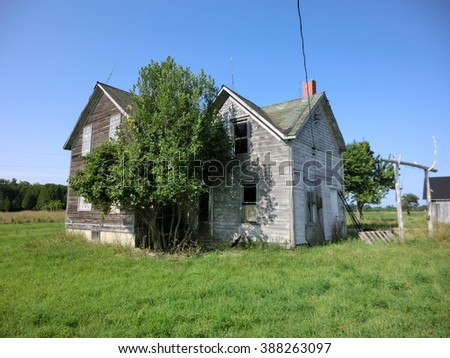 Abandoned weathered wooden farmhouse exterior - landscape color photo - stock photo