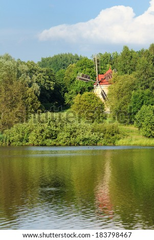Abandoned windmill on the coast of the pond - stock photo