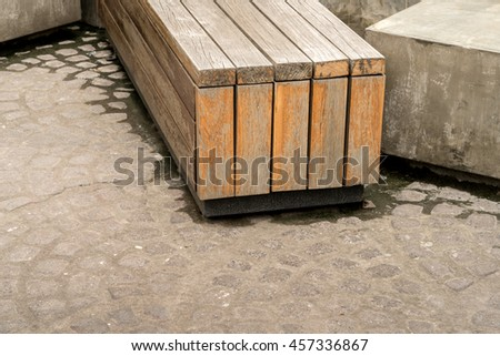 Abandoned wooden bench on concrete floor in the park - stock photo