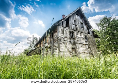 Abandoned wooden house surrounded by romantic nature - stock photo
