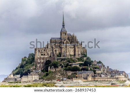 Abbey Mont Saint-Michel (7th century) at rocky tidal island in Normandy - one of most visited tourist sites in France. Mont-Saint-Michel and its bay are part of UNESCO list of World Heritage Sites. - stock photo