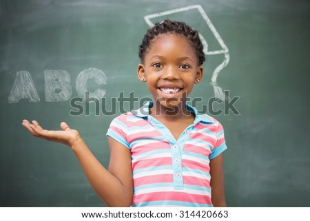 ABC against smiling pupil raising her hand - stock photo