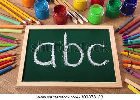ABC alphabet written in chalk on a small blackboard  - stock photo