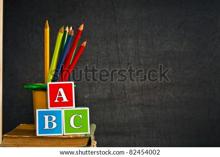 ABC and multicolored pencil on old textbook against blackboard in class. School concept - stock photo