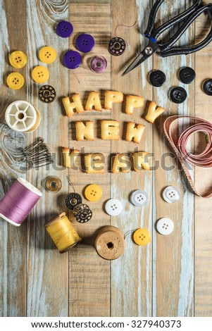 ABC Cookie in the form of word HAPPY NEW YEAR and sewing tools on vintage wooden background. Copy-Space - stock photo