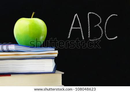 ABC written on a blackboard with books and apple in front - stock photo