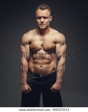 Abdominal shirtless muscular guy isolated on a grey background. - stock photo