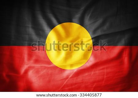 Aboriginal Australia flag on grunge fabric - stock photo