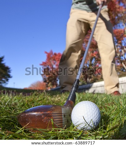 About to hit a fairway wood with an old, traditional wood club on a beautiful fall day. - stock photo