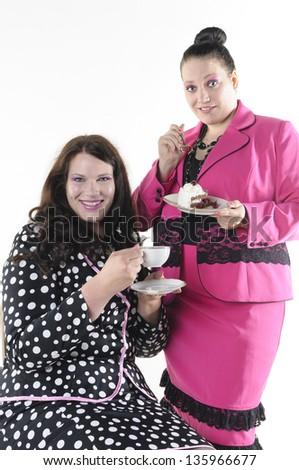 About two faithfully models wear flashy costumes and chat over coffee and cake, isolated against white background. - stock photo