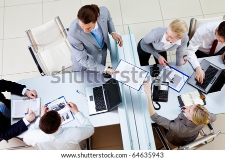 Above angle of confident man passing contract to pretty secretary in working environment - stock photo