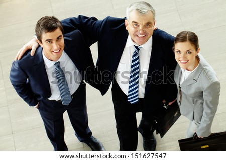 Above angle of joyful business group looking at camera  - stock photo