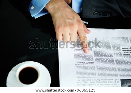 Above angle of male hand pointing at article in newspaper with cup of coffee near by - stock photo