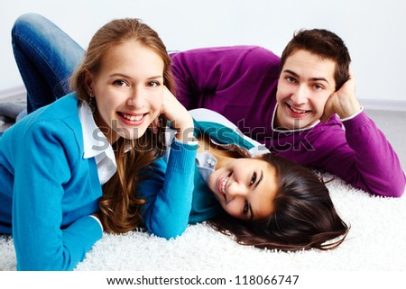 Above angle of three laughing friends looking at camera and smiling - stock photo