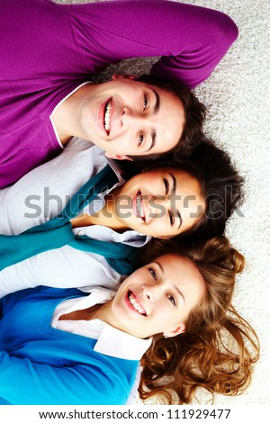 Above angle of three laughing friends lying on the floor and looking at camera - stock photo