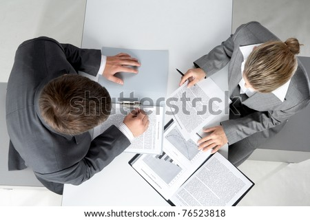 Above angle of two business partners planning work at meeting - stock photo