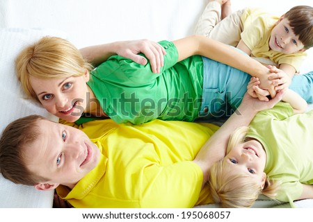 Above angle of young family looking at camera and smiling - stock photo
