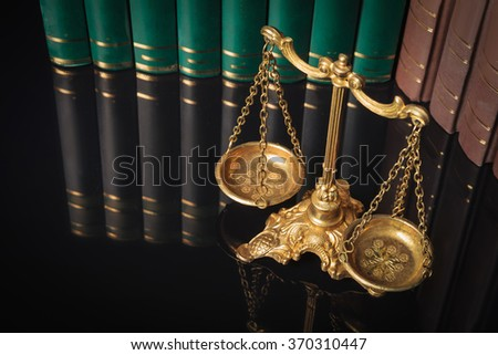 above picture of a golden justice scales in front of law books  - stock photo