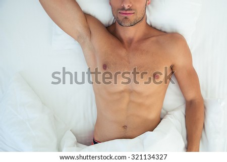 Above portrait of a male body sleeping on the bed - stock photo