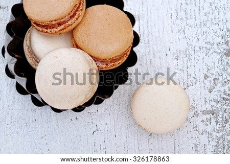Above shot of chocolate and vanilla macarons over a rustic wooden background. Shallow depth of field. - stock photo