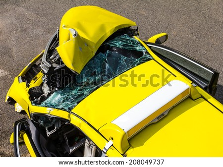 Above the ruins of the yellow car collision accident on the road  - stock photo