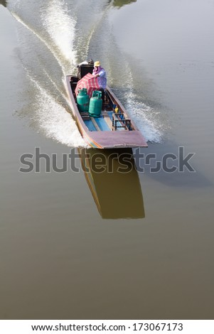 Above the wooden boats and small engines rumbled to come to us  - stock photo