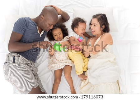 Above view of a big mixed family lying on the bed, parents playing with their little children  - stock photo