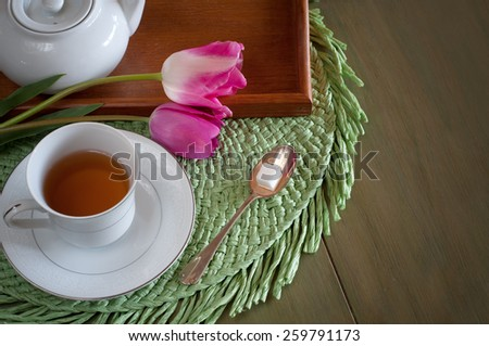 Above View of a Pretty and Colorful Spring, Easter, or Mothers Day, Tea Place Setting and Pink Tulips, Cup, Spoon, Sugar.  Room or Space for Copy, Text, your Words.  Horizontal looking down, aerial. - stock photo