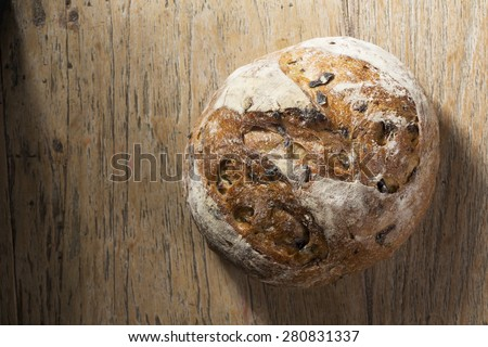 Above view of a rustic loaf of bread on an old wooden table. - stock photo