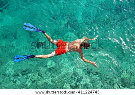 Above view of a snorkeling man in the tropical sea - stock photo