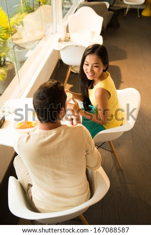 Above view of a young couple spending their free time at a cafe  - stock photo