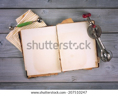 Above View of Antique Recipe Book with room or space for text, copy, words.  Vintage hand mixer and melon baller utensils.  Vignette horizontal on textured gray wood boards - stock photo