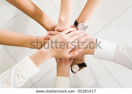 Above view of business partners hands on top of each other symbolizing companionship and unity - stock photo