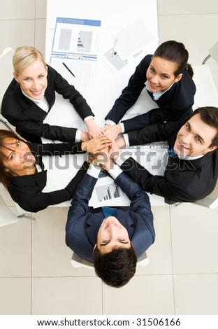 Above view of business people with their hands on top of each other and looking upwards - stock photo