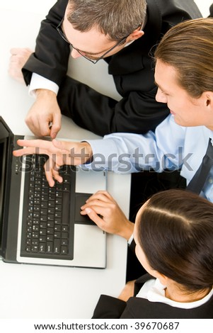 Above view of business people working with laptop - stock photo