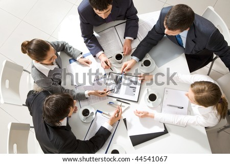 Above view of business team sitting around table and discussing working plan - stock photo