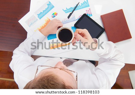 Above view of businessman working during coffee break - stock photo