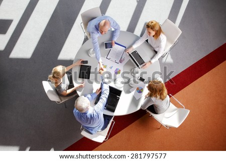 Above view of businessmen shaking hands while sitting at meeting with business people and make a deal. - stock photo