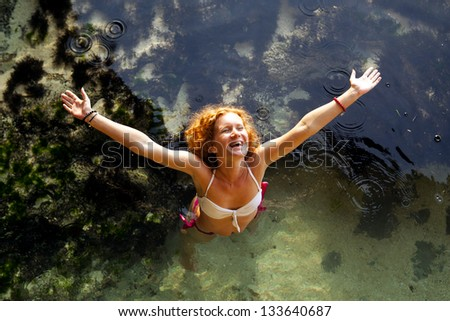 Above view of cheerful young woman raising her hands and standing in water - stock photo